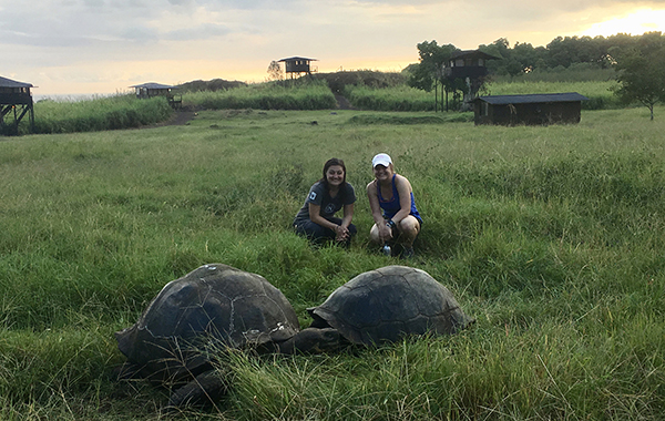 Sisters in the Galapagos with tortoises.