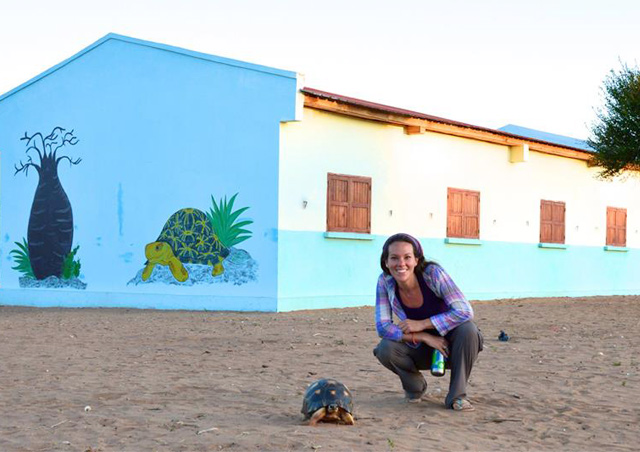 Corrin in remote Madagascar with the rare radiated tortoise, in front of a newly erected school in a village where no school had ever previously existed.