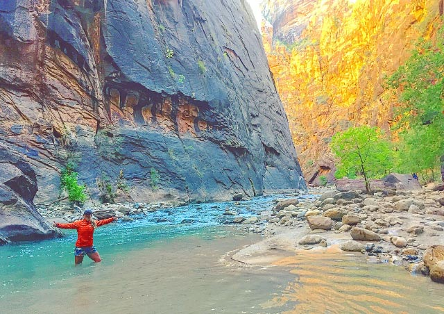 Embracing the icy cold water of the Narrows in Zion National Park.