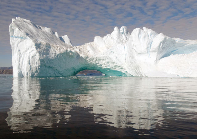 Surreal icebergs reflect Caribbean hues in East Greenland's frigid Sermilik Fjord.