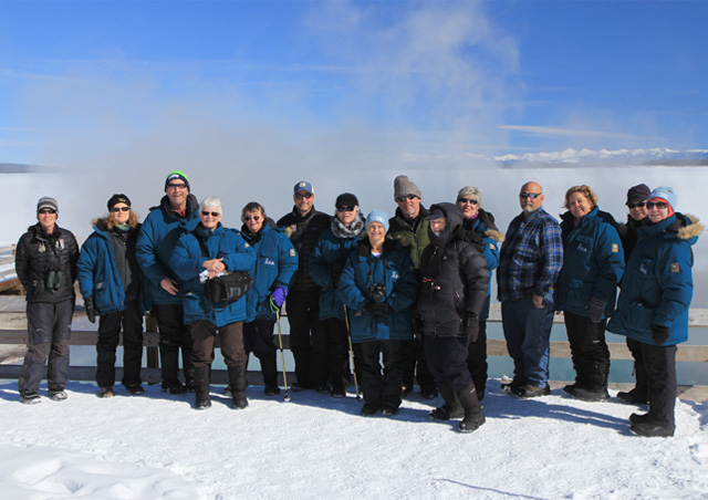 A happy Nat Hab group enjoys a sunny winter day on the shores of Yellowstone Lake