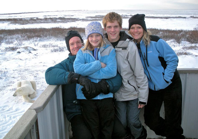 My family enjoying a Classic Polar Bear Adventure in Churchill, on the viewing platform aboard our Polar Rover vehicle. Note who's resting on the ground to our left.