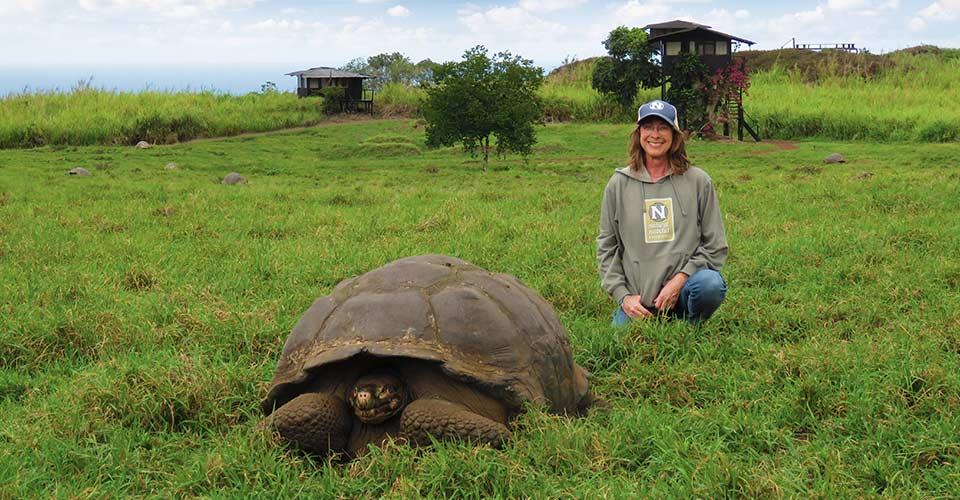 A traveler poses next to a giant tortoise at Natural Habitat's Tortoise Camp, Santa Cruz, Galapagos Islands, Ecuador