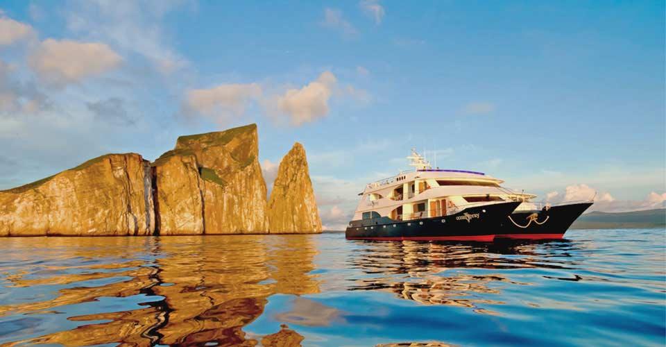 The M/C Ocean Spray cruises near Kicker Rock in the Galapagos Islands, Ecuador