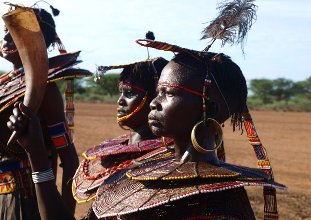 Remote Pokot tribe in the Northern Frontier District. This particular tribe had only seen white folk three other times. The women were wearing calf skin skirts, and beads made of hardened clay which were painted, and the men also had calf skin on and ostrich feathers in their headdresses.
