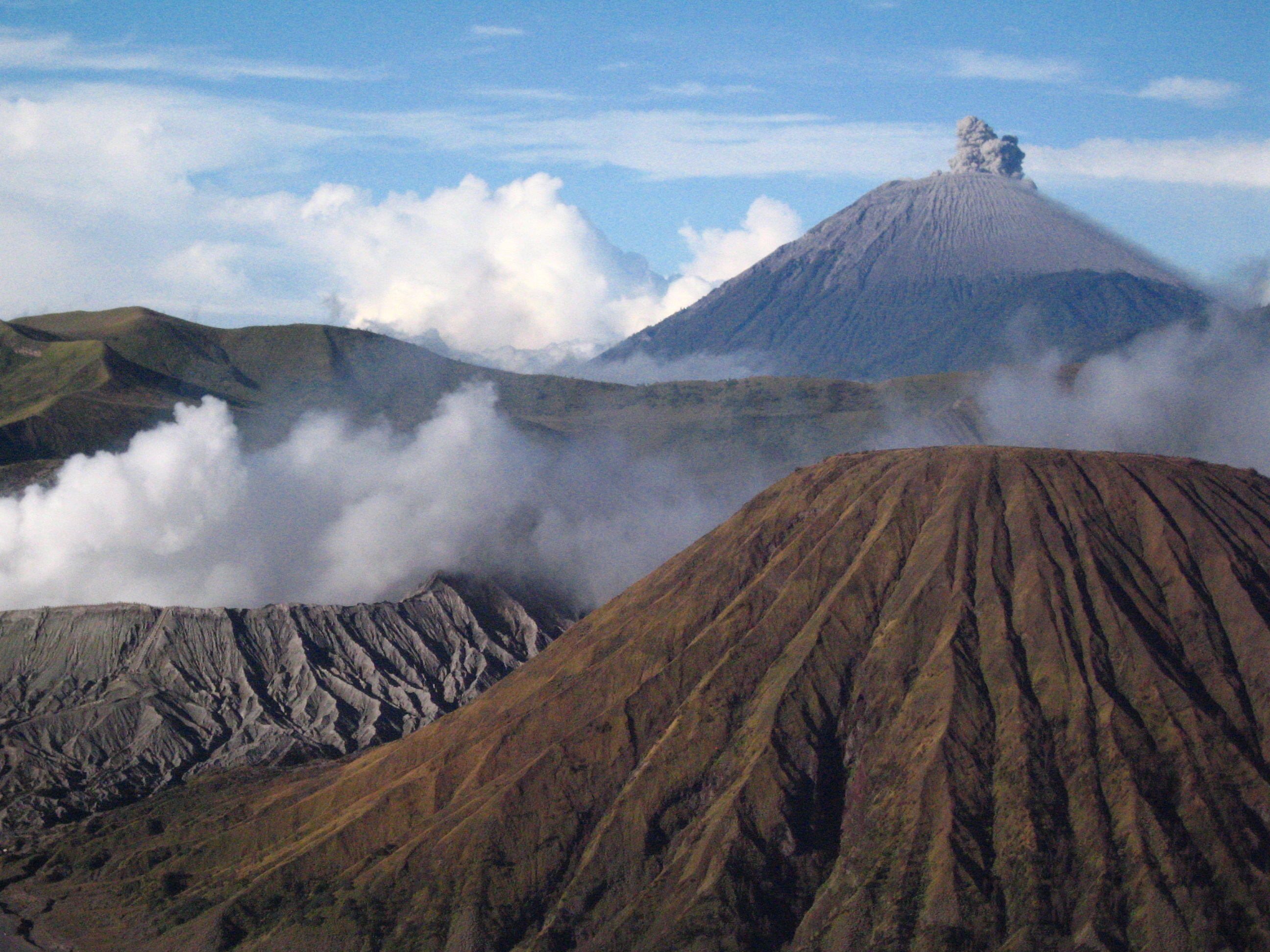This is a sunrise view from atop Mt. Pananjakan in Java, Indonesia. Clockwise from lower left is the steaming crater of Mt. Bromo, erupting Mt. Semeru, and the stately Mt. Batok.