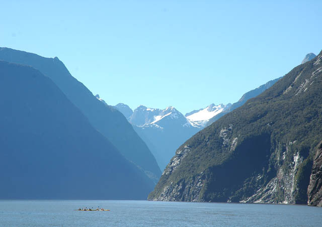 The majestic Milford Sound on New Zealand's south island, where snowy peaks and waterfalls surround you. It is often cloudy and rainy here on the south island's west coast; a clear day like this one is uncommon – what luck!