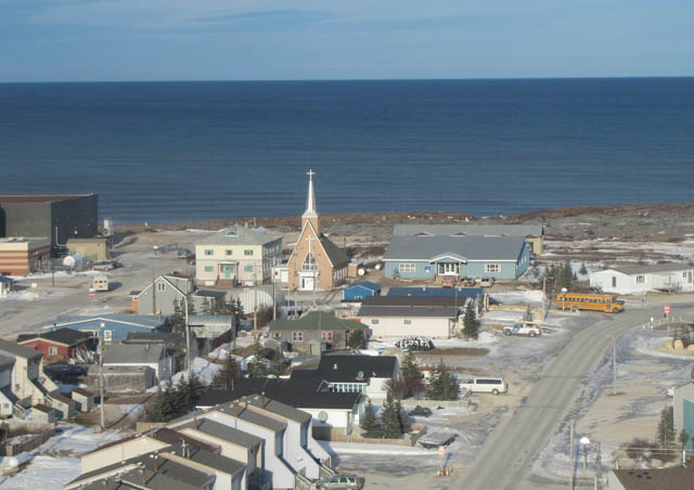 Churchill, Canada. This small town on Hudson Bay is home to many arctic cultures and smack-dab in the middle of the polar bears' migration to the ice floes every October & November.